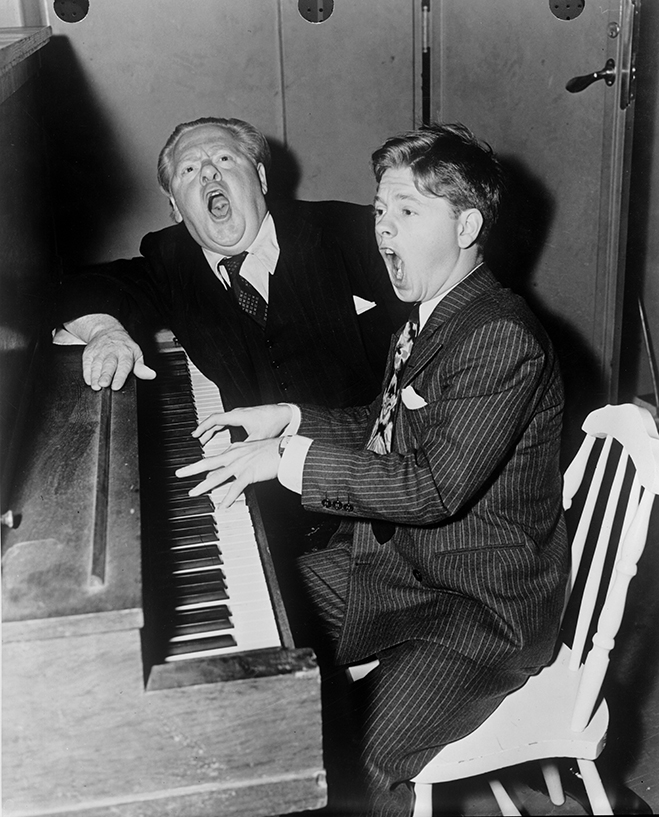 Medium shot of Mickey Rooney sitting at and playing piano with his father, character actor Joe Yule. Both are singing back stage of an MGM set, March 1940.