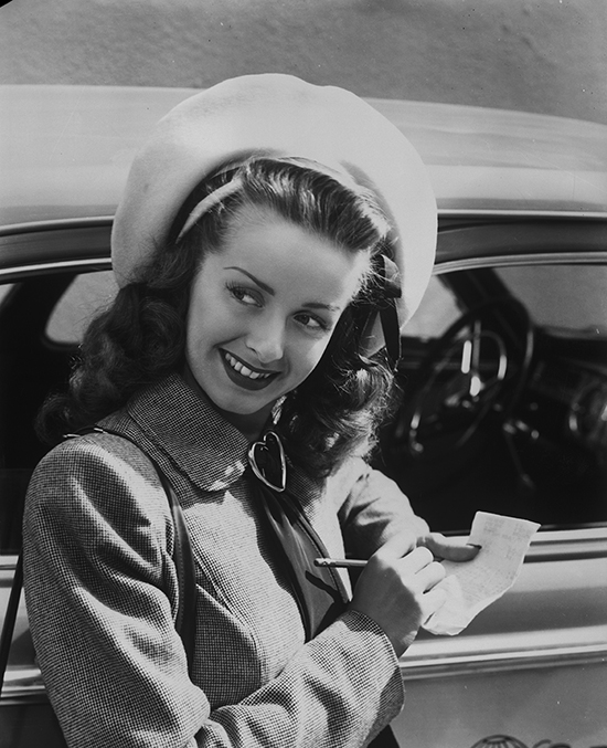 Medium shot of Noel Neill as Lois Lane, wearing hat, taking notes.