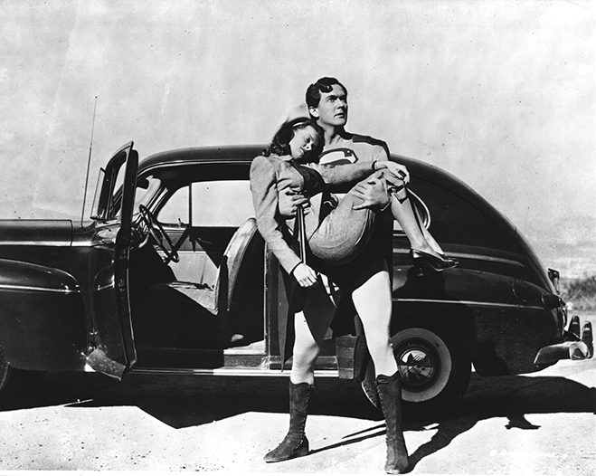 Kirk Alyn as Superman/Clark Kent holding Noel Neill as Lois Lane in front of car.