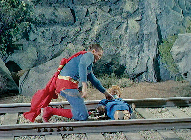 George Reeves as Superman rescuing Noel Neill as Lois Lane from train tracks