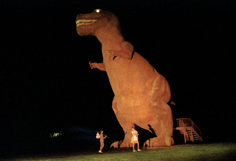 Pee-Wee (Paul Reubens) and Simone (Diane Salinger) standing under the giant T. Rex statue filmed on location in Cabazon, California.