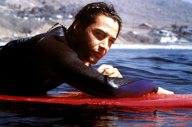 Keanu Reeves takes a rest on his board in the 1991 surprise action hit, Point Break, which has become a cult classic.
