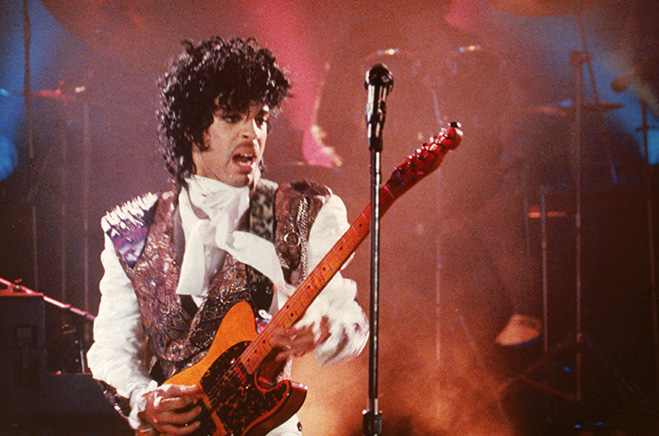 Prince as The Kid playing guitar onstage.