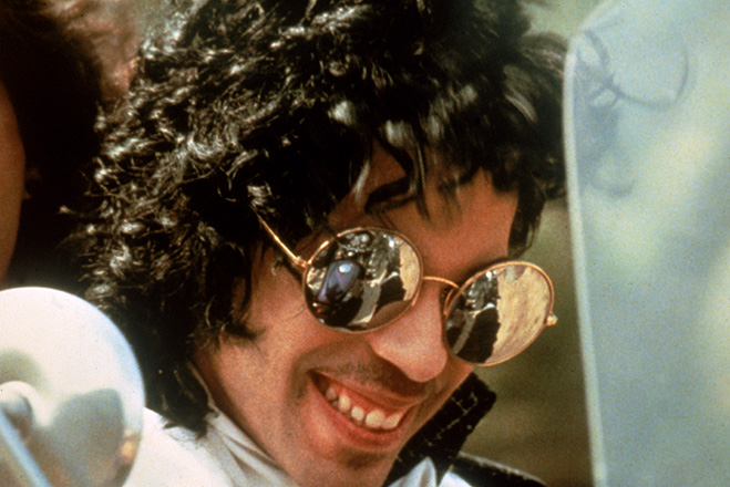 Prince as The Kid, wearing mirrored sunglasses on motorcycle.