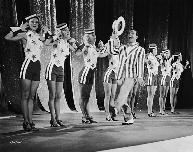 "Gene Kelly as Don Lockwood singing and dancing on stage with other performers during musical number ""Broadway Melody Ballet."""