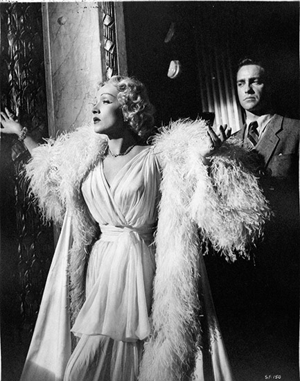 Marlene Dietrich as Charlotte Inwood wearing nightgown, standing with Richard Todd as Jonathan Cooper.