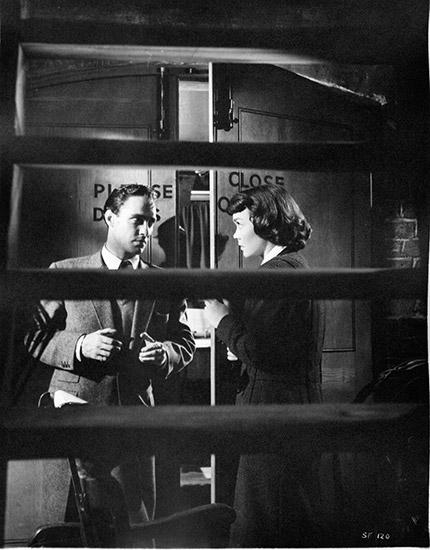 Medium shot through ladder of Richard Todd standing with Jane Wyman as Eve Gill.