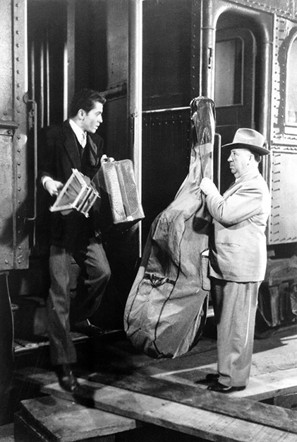 Farley Granger as Guy Haines standing on departing train holding tennis racquet, suitcase and looking at director Alfred Hitchcock (in cameo), boarding train and holding double bass.