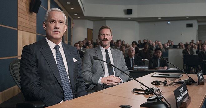 "Tom Hanks as Captain Chesley ""Sully"" Sullenberger and Aaron Eckhart as First Officer Jeffrey Skiles appear before the NTSB in Sully."