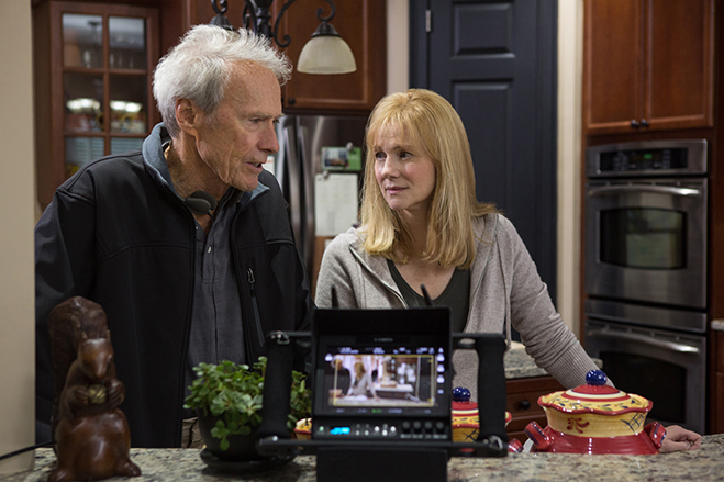 director clint eastwood and laura linney (as Lorrie Sullenberger) discuss a scene on the set of Sully.