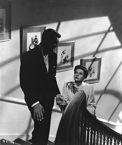 Full shot of Cary Grant as Johnnie leading Joan Fontaine as Lina upstairs.