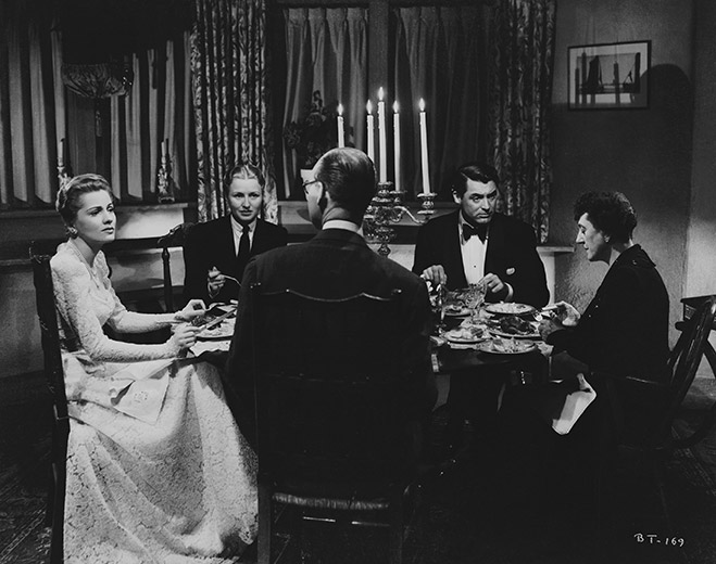 Wide angle shot of dinner table with Joan Fontaine as Lina McLaidlaw Aysgarth, Nondas Metcalf as Phyllis Swinghurst, Cary Grant as Johnnie Aysgarth, Auriol Lee as Isobel Sedbusk and Gavin Gordon as Bertram Sedbusk