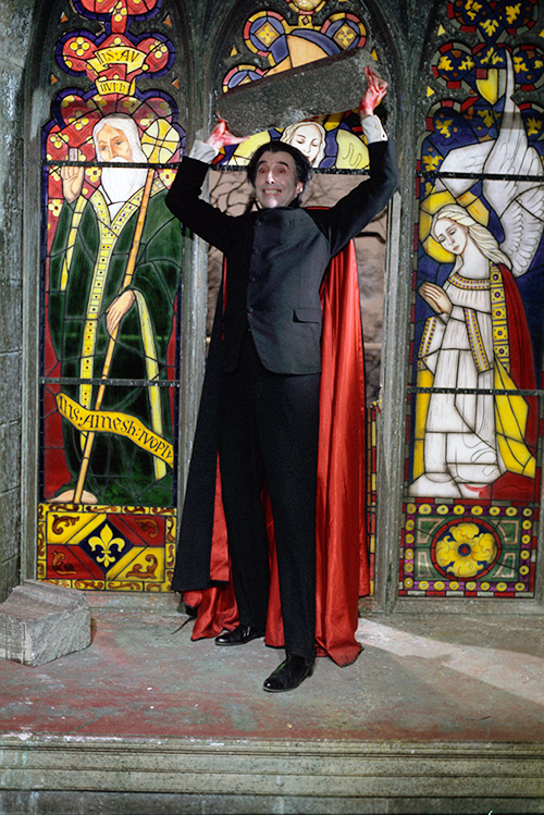 Christopher Lee as Count Dracula in front of stained glass window