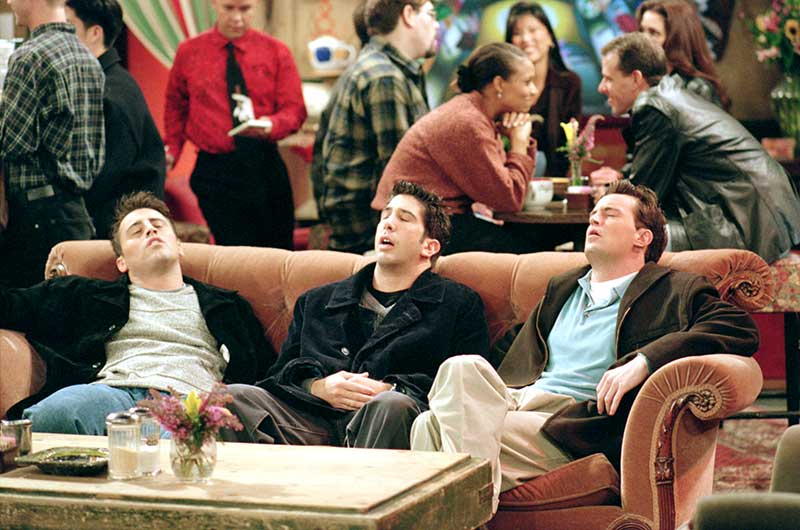 "Matt LeBlanc as Joey, David Schwimmer as Ross, and Matthew Perry as Chandler, sitting on couch with eyes closed, in Central Perk coffee house from episode ""The One Where They're Going To Party""."