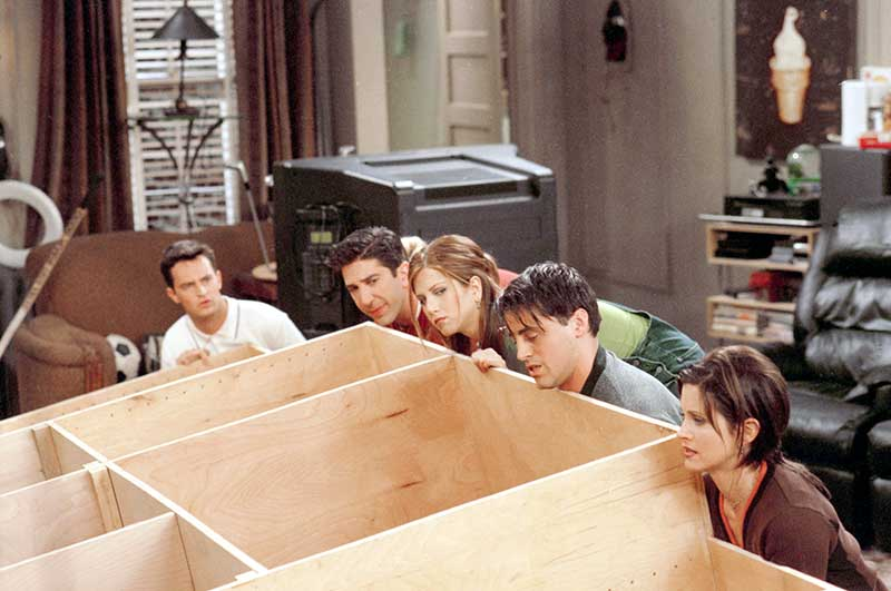 "Matthew Perry as Chandler, David Schwimmer as Ross, Jennifer Aniston as Rachel, Matt LeBlanc as Joey, and Courteney Cox as Monica, all lifting entertainment center in episode ""The One With Frank Jr.""."
