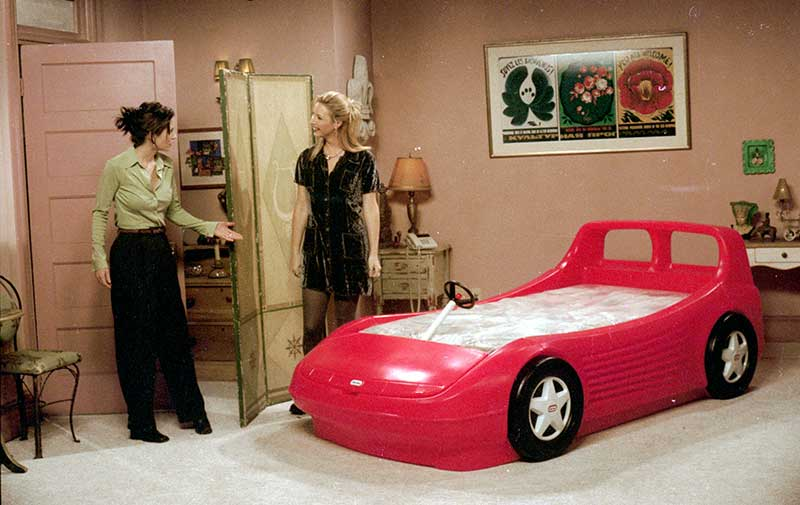"Courteney Cox as Monica and Lisa Kudrow as Phoebe in bedroom with red racecar bed in episode ""The One With The Race Car Bed""."