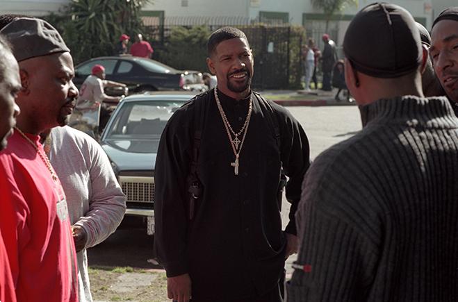 Medium shot of men watching Denzel Washington talking with Bone as Bench Presser at extreme right