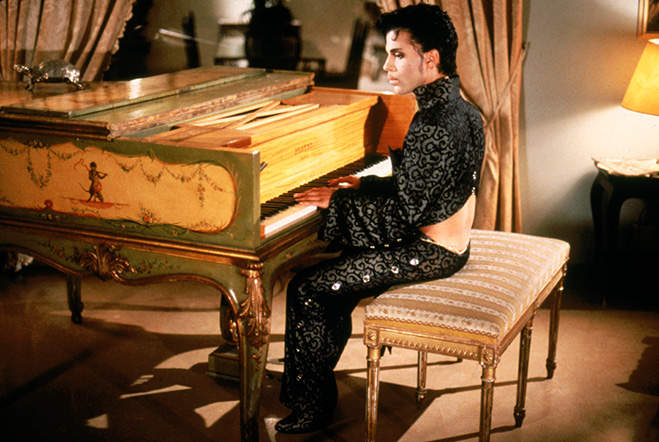 Prince as Christopher Tracy, seated at ornate, gilded piano.