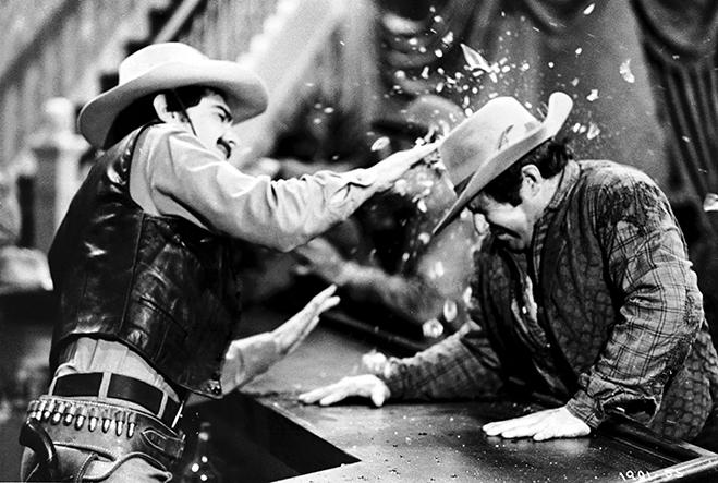 "Medium shot of Richard Benjamin as Peter Martin, wearing cowboy hat, hitting ""robot"" over head with liquor bottle."