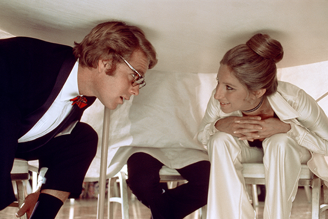 Ryan O'Neal as Howard Bannister and Barbra Streisand as Judy Maxwell crouched under table.
