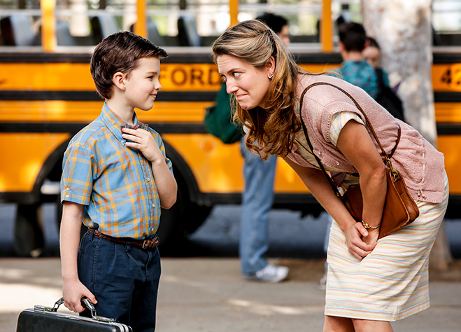 Zoe Perry and Iain Armitage in Young Sheldon in front of yellow school bus.